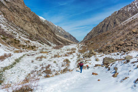 Idyllic winter landscape with hiking trail in the mountains. Rocks, snow and stones in mountain valley view. Mountain panorama.