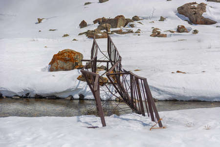 Old destroyed bridge in mountains. Kyrgyz Alatoo mountains.