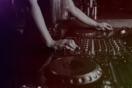 Hands of female DJ adjusting sound during disco party. Entertainment concepts equipment