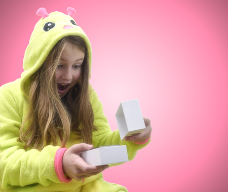 Happy, emotional girl in pajamas received a smartphone as a gift. Isolated on Pink background