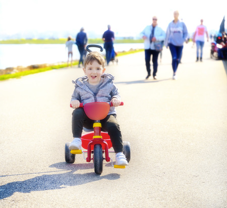 A little happy boy rides on red tricycle on a  street looking at camera