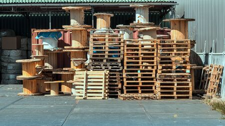 Stacked wooden pallets and wooden coil of electric cable on warehouse. Factory warehouse