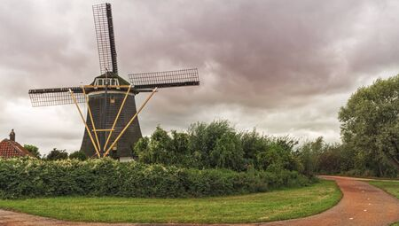 Old wind mill  at the dramatic cloudy sky in Holland. The Netherlands