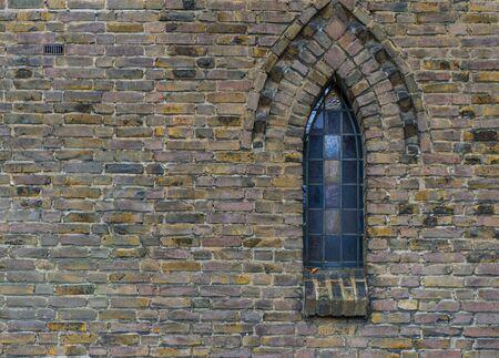 Vintage staned glass at the old castle. Surface old bricks wall. Reklamní fotografie - 133803648