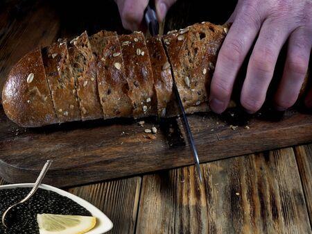 Closeup view of chef slicing bread on wooden cutting board. Cutting a bread. Reklamní fotografie