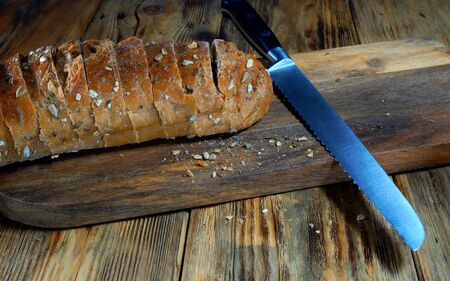 Sliced brown bread lies on a wooden cutting board.