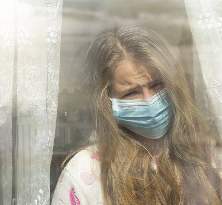 Sad girl in protective medical mask looks out the window. Sadness child at home in isolation