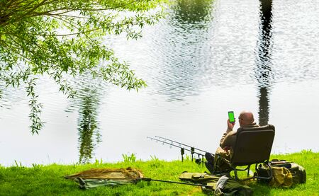 A fisherman is talking on the smartphone while fishing.Smartphone with green screen