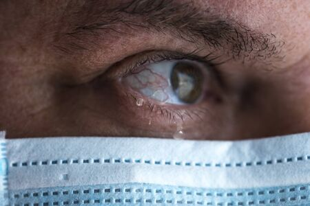 Tears in eyes of crying male doctor in mask. Face close-up. Pandemic and virus epidemic. Coronavirus covid-19. Tears in eyes.