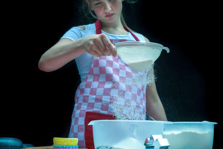 Selective focus. Girl sifting flour adding baking ingredients. Home bakery