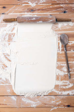 Flour scattered on the wooden table. Flour on the table surface. Baking background Reklamní fotografie