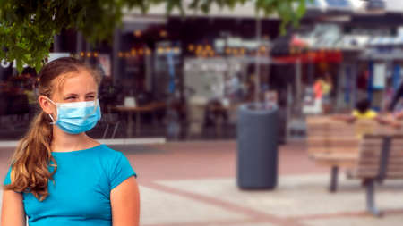 A young girl wears a face mask on the streets of the city.Cute Teenage Girl with a surgical mask on her face that protects against the spread of coronavirus disease. Archivio Fotografico