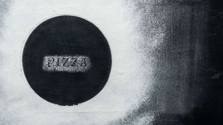 Flour and Text PIZZA on old shabby black baking sheet. Baking background. Top View