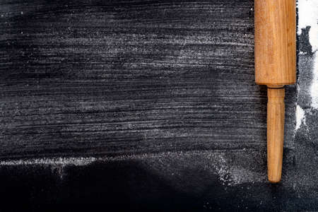 Rolling pin and Wheat Flour on a dark background. Free space for text. Top View
