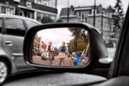 People on the bicycles in the city traffic .. View in the side mirror of the car. Cyclists on the city road. Archivio Fotografico