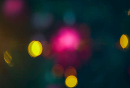 Defocused blurred festive bokeh lights. Blurred garland on Christmas tree as background .. New Year and Christmas holidays