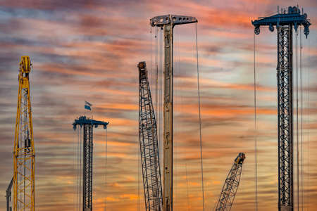 Tower cranes works on building site on the sky background at sunset. Construction site at sunset