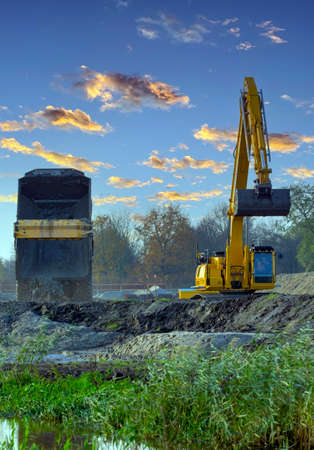 Yellow excavator works on construction site. Excavator shovel digs up soilon nature background Archivio Fotografico