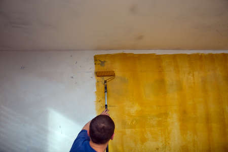 Worker at construction site applys yellow primer to the walls. Renovation concept Archivio Fotografico
