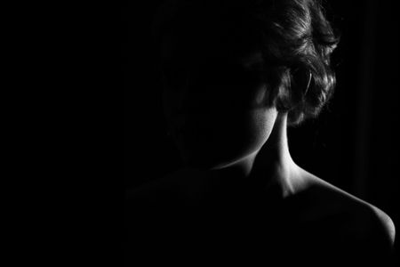 earnest: neck of young girl on black background with soft light