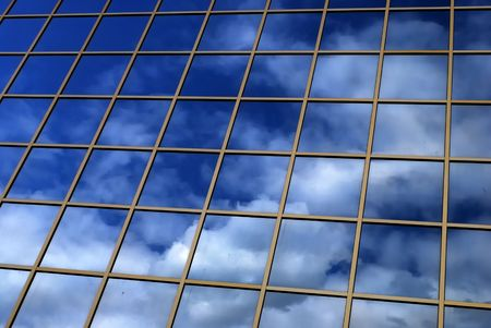 a mirror reflection of sky and clouds is in the windows of building Stock Photo - 3084610
