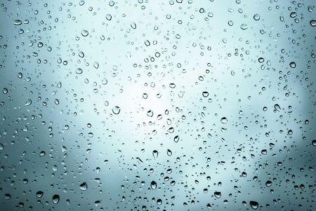 rain shower: rain drops on a window and mystic silhouette of city Stock Photo