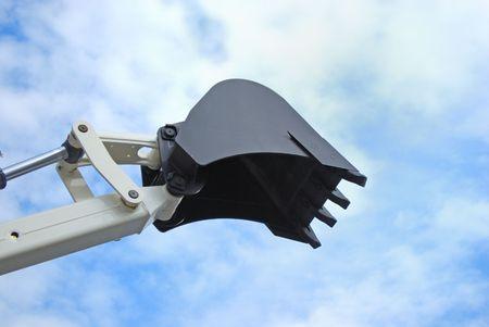 scoop of power-shovel is on cloud sky photo
