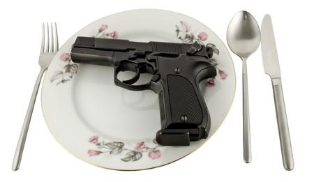 Pistola en una placa sobre la mesa sirvió aislada sobre fondo blanco Foto de archivo - 4067069