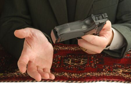 tyrant: hands of man on an east carpet with a pistol