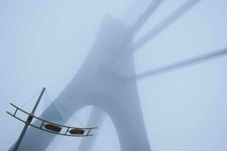 lugubrious: industrial constructions are in fog, details of bridge are in a grey color