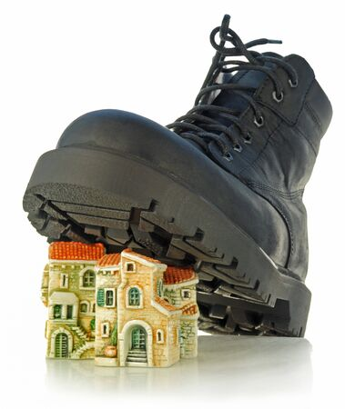 Rough boot on a high thick sole treads on houses Stock Photo