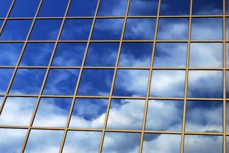 a mirror reflection of sky and clouds is in the windows of building Stock Photo - 4237936