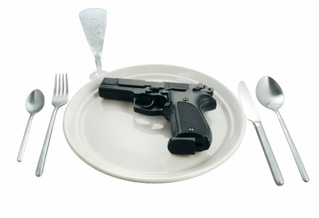 Pistol in a plate on the served table isolated on white background photo