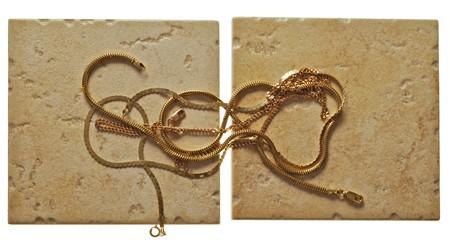 joyas de oro: chainlets de oro se encuentran en el mal trato de piedra Foto de archivo