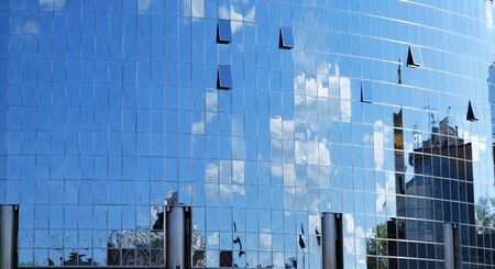 a mirror reflection of sky and clouds is in the windows of building Stock Photo - 4534054
