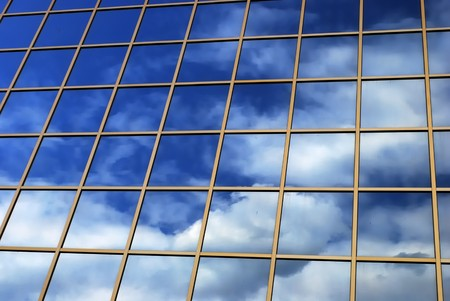 a mirror reflection of sky and clouds is in the windows of building Stock Photo - 4534092
