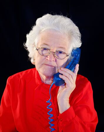 portrait of elderly woman is in red with an dark blue telephone Stock Photo - 4632264