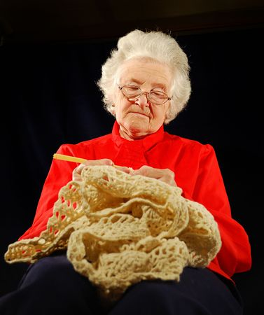 portrait of elderly woman is in red with  hook knitting (wool) photo