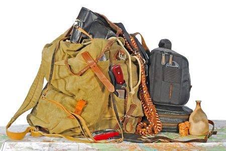 old traveller equipment : backpack, passport, knife, map, camera, chinks, souvenirs