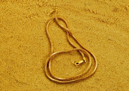joyas de oro: chainlets oro están en la arena suelta amarillo Foto de archivo