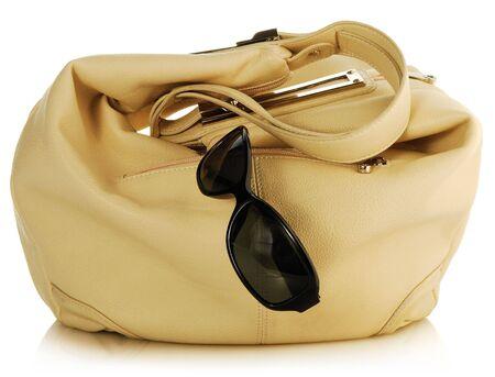 female light handbag and antisun glasses on white photo