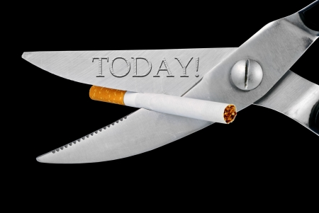 scissors cut a cigarette, isolated on a white background photo