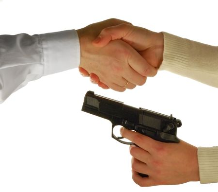 Handshake under a barrel of a pistol, isolated on white photo