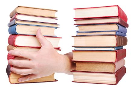 bibliomania: pile of old books and hand on a white background Stock Photo