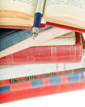 bibliomania: pile of old books and pen on white