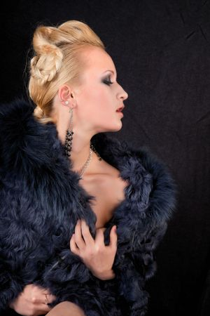 girl in a fur coat on a black background photo
