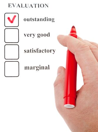 marginal: mans hand holding a red felt-tip on form of evaluation Stock Photo