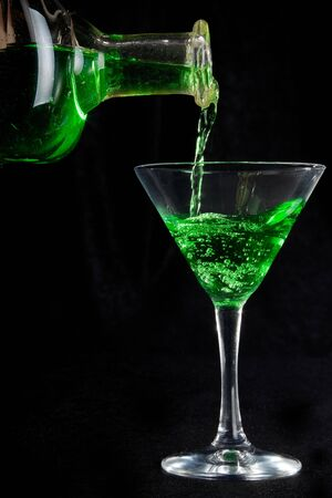 glass of green cocktails and bottle on black photo