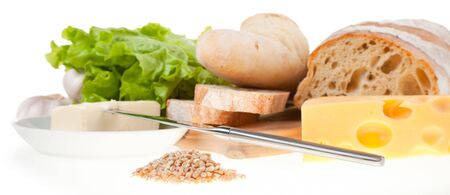 still life: table knife, lettuce, bread, cheese, butter and handful of wheat grain in focus photo