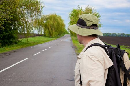 brisk: brisk tourist with a poster on a country road Stock Photo